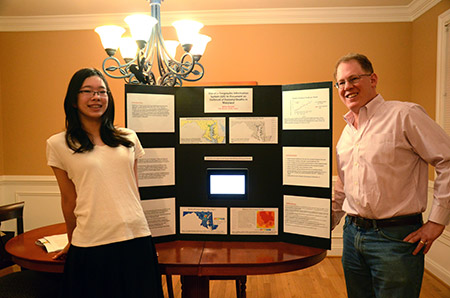 Sydney and Russell Alexander pose with the project Sydney did in sixth grade that led to closer collaboration  between the Office of the Chief Medical Examiner and a public health impact award at the National Association  of Medical Examiners conference in October. (Marc Shapiro)