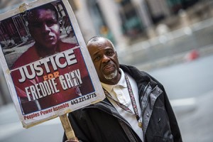 A protester carries a sign outside the City Circuit Court House during jury deliberations in the trial  of William G. Porter.