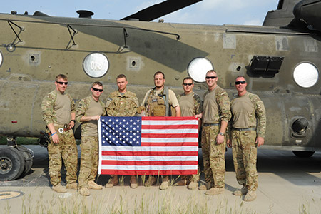 Robert L. Cunningham (center) poses for a photo with soldiers from a CH-47 crew attached to Task Force Tigershark in Salerno, Afghanistan.
