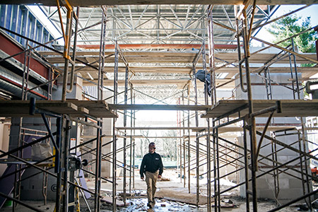 John Boelker, superintendent with Oak Contracting, walks through the construction of what will become Pikesville High School's new front entrance. (Mark Shapiro)
