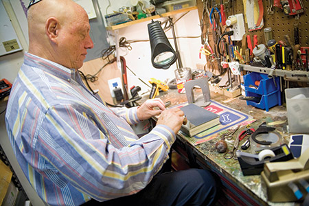 Arnie Feiner repairs a prayer book in his basement workshop. He estimates that he has repaired around 10,000 books. (Photo by Marc Shapiro)