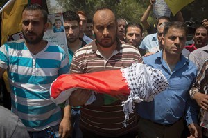 The body of 18-month-old Ali Dawabsheh, surrounded by relatives, is carried at her funeral in the Palestinian village of Duma. (Oren Ziv/Getty Images)