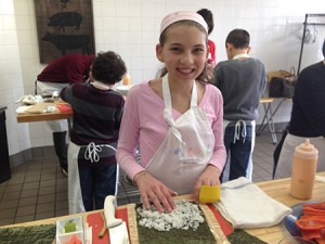 Katie Halushka, 14, prepares to roll sushi as a part of the Kids Cook summer camp at For the Love of Food in Pikesville. (Provided)