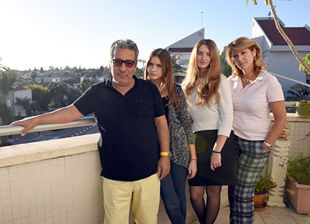Catherine Berdah, pictured here with her husband and daughters at their apartment in Raanana, Israel, went from making $6,000 a month as a pharmacist to $6 an hour as a cashier. (Photo: Cnaan Liphshiz)