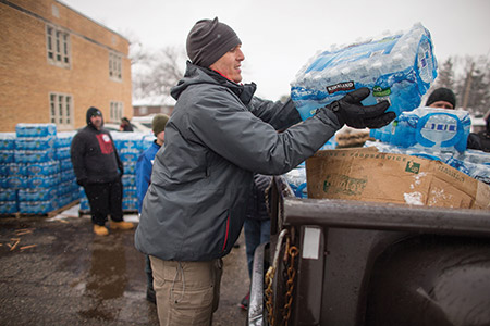 Volunteers loading cases of free water into waiting vehicles at a water distribution center in Flint, Mich., this month. (Geoff Robins/AFP/Getty Images)