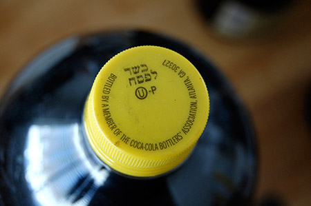 A kosher-for-Passover bottle of Coca-Cola is distinguished from ordinary Coca-Cola bottles by its yellow cap and the Hebrew words Kosher for Passover. (Columbia University Press)