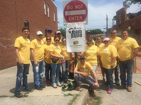 Employees from Klein Enterprises, a Pikesville-based commercial and residential real estate development and management firm, volunteered with Habitat for Humanity of the Chesapeake on Wednesday, June 22, painting fences and building concrete landings in the backyards of homes in the Woodbourne-McCabe neighborhood in North Baltimore. (provided)