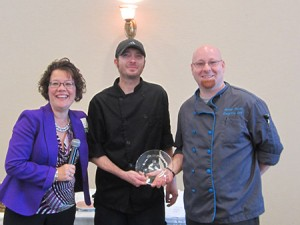 TOP CHEF: Cindy Wolf, director of sales and marketing at North Oaks Senior Living Community, awards Chef Nate Finney (right) and Cook Matthew Peach with the first- place prize in North Oaks' annual Battle of the Chefs, an event in which community members taste dishes from competing chefs and vote for their favorite based on taste, creativity and presentation. (Provided)