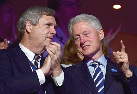 """Former President Bill  Clinton, wearing a button that says """"Hillary"""" in  Hebrew, shares some thoughts with Secretary of Agriculture Tom Vlsack at the 2016 Democratic  National Convention in Philadelphia. (Ron Sachs/dpa/picture-alliance/Newscom)"""