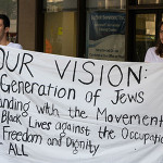 IfNotNow protesters hold a large banner with their message in an  attempt to attract the attention of people walking into the building that houses the American Jewish Committee. (Justin Katz)