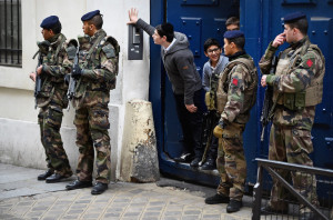 PARIS, FRANCE - JANUARY 13:  Children look out from a doorway as armed soldiers patrol outside a School in the Jewish quarter of the Marais district on January 13, 2015 in Paris, France. Thousands of troops and police have been deployed to bolster security at 'sensitive' sites including Jewish schools. Millions of people converged in central Paris  for a Unity March joining in solidarity with the 17 victims of last week's terrorist attacks in the country. French President Francois Hollande led the march and was joined by world leaders in a sign of unity. The terrorist atrocities started on Wednesday with the attack on the French satirical magazine Charlie Hebdo, killing 12, and ended on Friday with sieges at a printing company in Dammartin en Goele and a Kosher supermarket in Paris with four hostages and three suspects being killed. A fourth suspect, Hayat Boumeddiene, 26, escaped and is wanted in connection with the murder of a policewoman.  (Photo by Jeff J Mitchell/Getty Images)