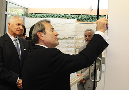 Steven Fader watches Beth Tfiloh Congregation Rabbi Mitchell Wohlberg hang a mezuzah at the  entrance of the new chapel. (Provided)