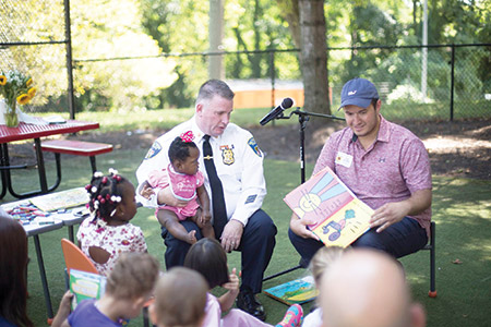 """STORY TIME: Major Richard Gibson, commander of the Baltimore  Police Department's Northern District, and Isaac """"Yitzy"""" Schleifer, the Democratic nominee for Baltimore City District 5 councilman, read  during story time at a """"family reunion"""" on Aug. 28 the Mt. Washington Pediatric Hospital hosted for families and former patients of the Center for Neonatal and Pediatric Transitional Care. (provided)"""