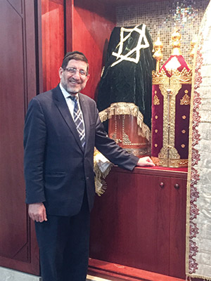 Daniel Golfeiz stands in front of a Torah box that stores Sephardic scrolls as a means of protection. Ashkenazi scrolls are freestanding. (Photo provided)