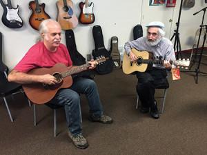Longtime customer Rick Sambuco (left) jams with Guitars of Pikesville owner Joshua Polak. Photo by Daniel Nozick