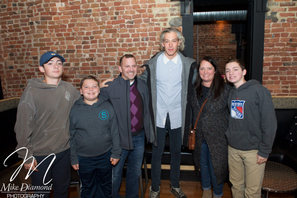 JCC of Greater Baltimore president  and CEO Barak Hermann (third from left) and his family smile with  Matisyahu prior to his performance at the Baltimore Shabbat Project's Community Havdalah Concert. From left: Jacob, Jonah, Hermann,  Matisyahu, Cory and Zachary. (Provided)