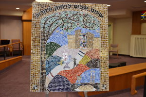 """On Saturday, Nov. 12, during a 60th  anniversary celebration, Beth Israel Congregation presented Rabbi Jay and Cindy Goldstein with a mosaic that was put together by members including preschoolers and learning lab students. The Hebrew phrase """"Shalom, shalom, larachoke v'lakorov"""" means """"peace, peace be upon those that are far and close."""" Parts of the mosaic were made by an artist in Baltimore's sister city Ashkelon, and the mosaic also features a  Shabbat table, Beth Israel's building and the Goldsteins and their three kids dancing on a talis that has actual tzit tzit tied by Rabbi Rachel Blatt and her husband. See next week's JT for more coverage of Beth Israel's 60th anniversary."""