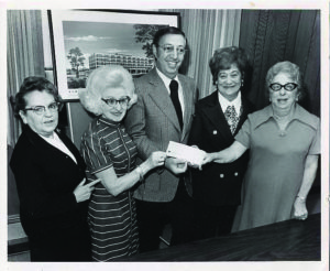 Joan Diskin and other women receiving a check, circa 1965.