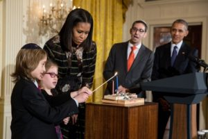 ELIJAH AND SHIRA WIESEL, GRANDCHILDREN OF THE LATE ELIE WIESEL, LIGHT THE MENORAH AT THE WHITE HOUSE CHANUKAH PARTY ON DEC. 14, AS PRESIDENT BARACK OBAMA AND FIRST LADY MICHELLE OBAMA LOOK ON. OFFICIAL WHITE HOUSE PHOTO BY CHUCK KENNEDY