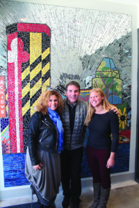 Art with a Heart executive director Randi Pupkin (left), Under Armour CEO Kevin Plank and Art with a Heart director of public art and community service Jenny Hyle pose in front of a newly installed mosaic at the Under Armour House at Fayette community center. The mosaic was created with 300 volunteers and depicts imagery and the skyline of downtown Baltimore. (Provided)