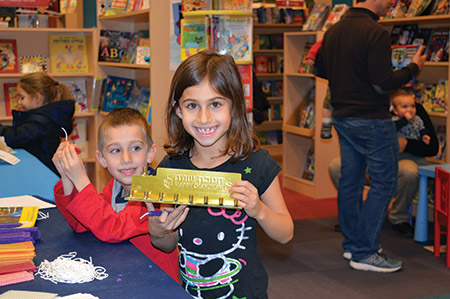 A happy girl proudly displays a menorah during a candle-making activity at the JCC of Greater Baltimore's Chanukah celebration at the Hunt Valley Towne Centre on Dec. 19, which also featured music, face painting, balloon art, storytime, dreidel spinning and holiday card making for the homeless.