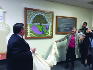 From left: William Vaugh, a vice president at Remedi  SeniorCare; Robin Rich, chair of the board of The Beacon Institute; and Mitch Markowitz, a vice president at Family & Nursing Care, Inc. unveil a mural dedicated to Mayer Handelman at the Handelman Conference Center in Columbia. The late Pikesville resident was a pioneer in elder care, and helped form the LifeSpan senior care association in the '80s.