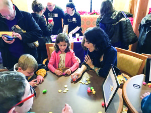 JCC interfaith engagement director Lara Nicolson plays dreidel with Ayelet Snyder at Foundry Row. (Photo by JCC)