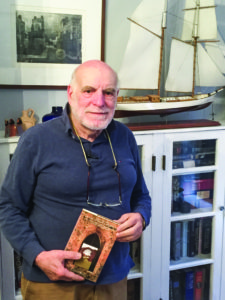 "Harry Ezratty holds a copy of his book, ""500 Years in the Jewish Caribbean."" (Photo by Daniel Nozick)"