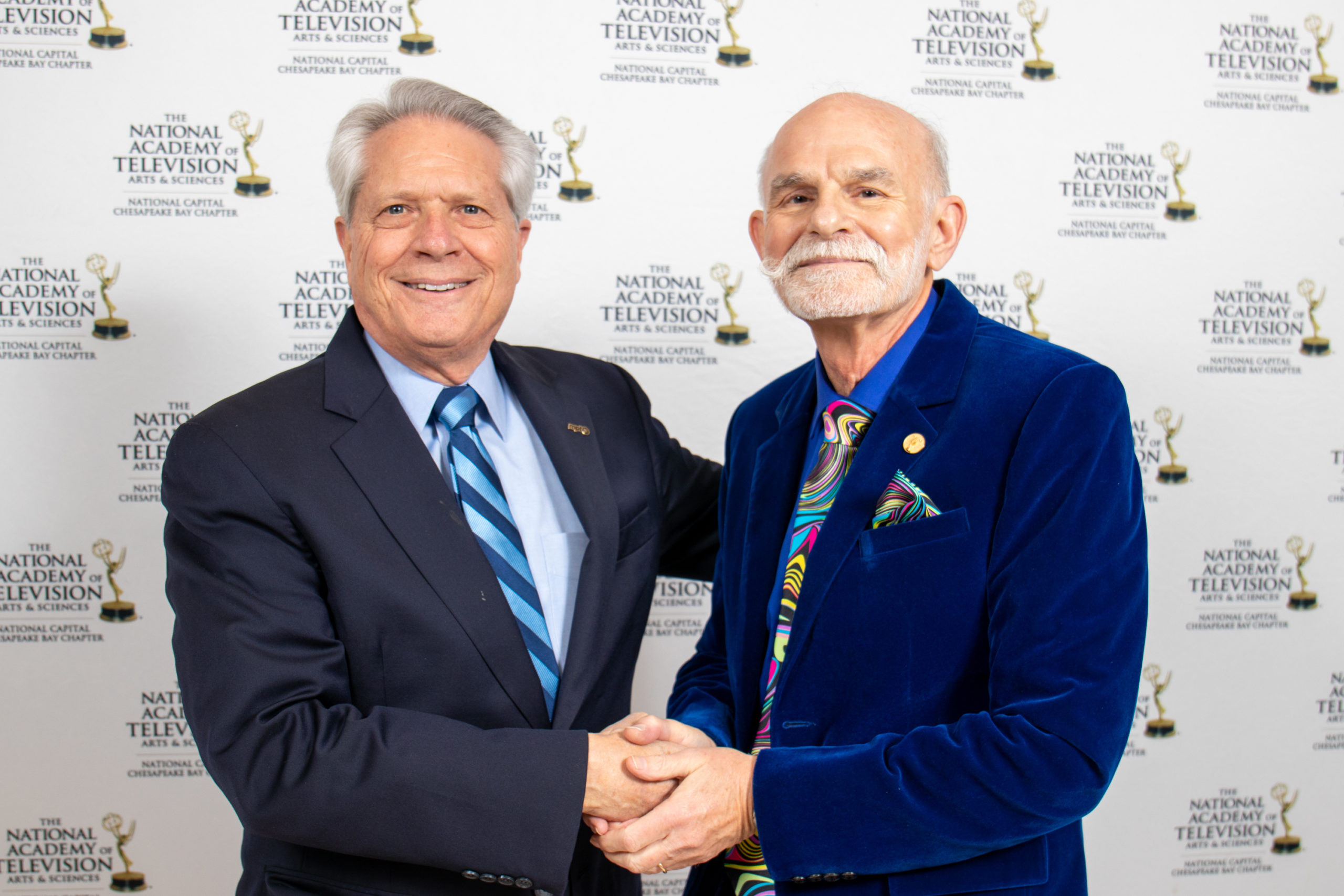 Senior vice president of Maryland Public Televsion George Beneman (right) accepted an award for his half-century dedication to local broadcasting. Here he shakes hands with CEO Larry Unger (Pete Estrada).