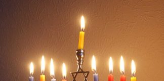 h: A contemporary Candelabrum (Menorah, Hebrew: מנורה) in the style of a traditional Menorah. Seen here with eight candles lit (the ninth candle is the service, Shamash, Hebrew: שמש), used during the Jewish Hanukkah holiday, 2014, United Kingdom. Photo by Gil Deke