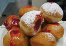 Classic Hanukkah sufganiyot filled with strawberry jelly and powdered sugar above (Noam Furer)