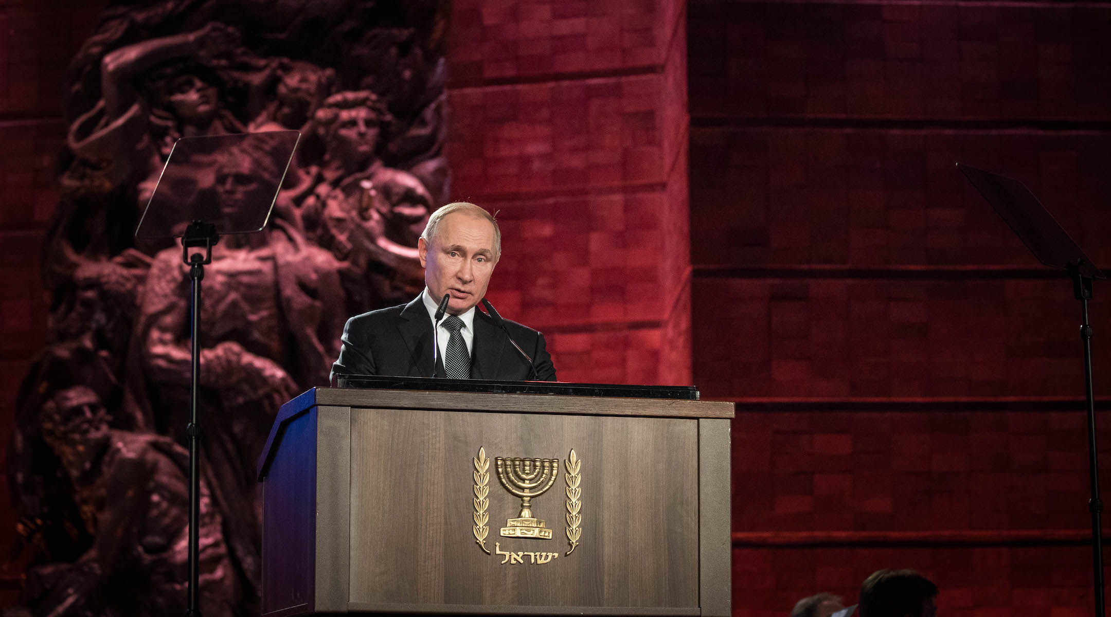 Russian president speaks from podium with emblem of Israel on it.