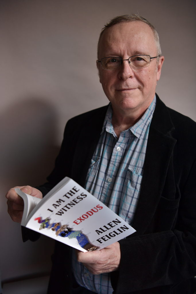 """66-year-old man in button down shirt and blazer, holding an open book. The cover says """"I am the Witness: Exodus."""""""