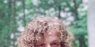 26-year-old woman with blond curly lob hairstyle and wide-scoopneck striped shirt. Wooded background.