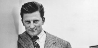 Greyscale portrait of actor Kirk Douglas in white shirt, tie, and sports coat.