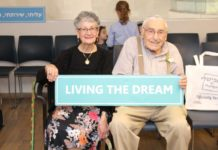"""Smiling elderly couple holds seafoam green sign with the words """"Living the Dream"""" on it."""