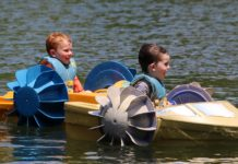 Two children in paddleboats on a lake.