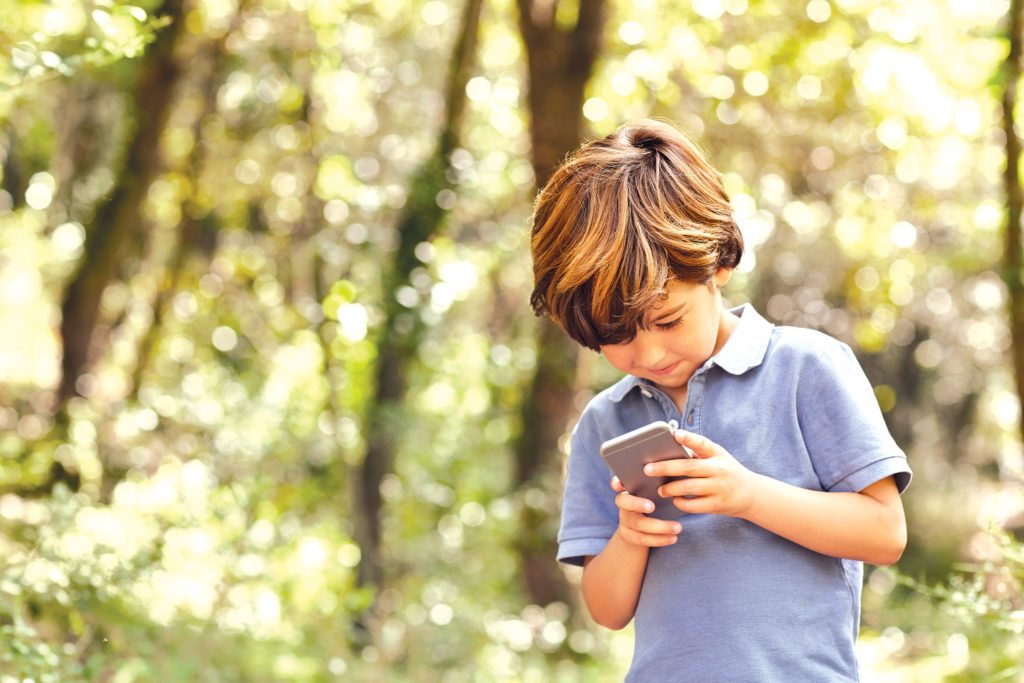 Smiling boy using mobile phone. Male is holding wireless technology.