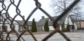 Close-up of rusty chain link fence next to an empty paved lot with houses on the perimeter.
