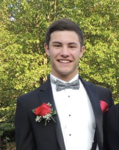 young max with dark hair in black tuxedo, white shirt, and bow tie, red rose in his lapel