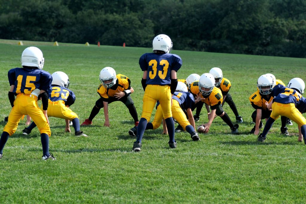 Children playing football in navy and gold uniforms and white helmets.