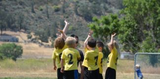 Children wearing yellow and black sports uniforms, standing in a tight circle in front of their coach on a soccer field, raise their hands.