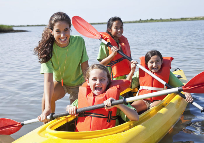 Teenage girl (17 years) helping children in kayak (8-9 years). Main focus on camp counselor and little girl in front.