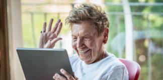 A very senior woman using digital tablet on apartment balcony