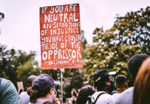 "backs of heads of people marching outside. one person is carrying a sign that says: ""If you are neutral in sitatuations of injustice you have chosen the side of the oppressor."" Desmond Tutu"
