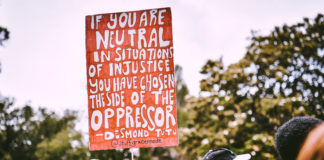 """backs of heads of people marching outside. one person is carrying a sign that says: """"If you are neutral in sitatuations of injustice you have chosen the side of the oppressor."""" Desmond Tutu"""
