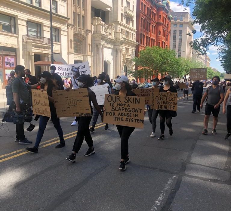 people marching down a DC street, holding up cardboard signs and wearing face masks