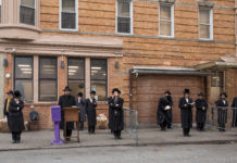 Hasidic men pray outside
