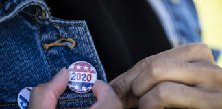 A young African American woman holding a voting badge. (LPETTET / iStock / Getty Images Plus)