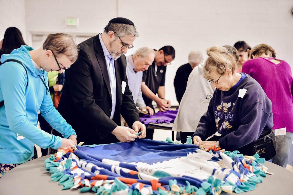 Participants of last year's Mitzvah Day program make no-sew blankets.
